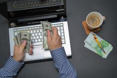 Uomo d'affari che lavora al computer portatile e che conta soldi mentre come beve il caffè Immagini Stock Libere da Diritti