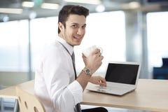 Uomo d'affari che lavora al computer portatile ed al caffè della bevanda Fotografia Stock Libera da Diritti