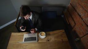 Uomo d'affari che lavora al computer portatile ed al caffè bevente sul caffè Vista superiore stock footage