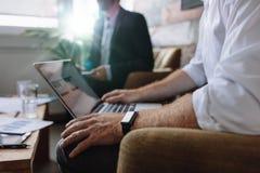 Uomo d'affari che lavora al computer portatile nel corso della riunione corporativa Fotografie Stock