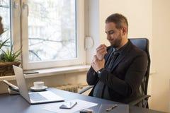 uomo d'affari che lavora al computer portatile nel dolore del polso dell'ufficio fotografie stock
