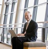 Uomo d'affari che lavora al computer portatile nell'ingresso dell'ufficio Fotografie Stock Libere da Diritti