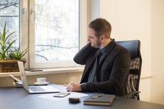 Uomo d'affari che lavora al computer portatile nella ferita del collo dell'ufficio fotografie stock