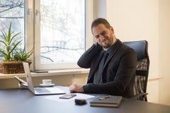 Uomo d'affari che lavora al computer portatile nella ferita del collo dell'ufficio immagine stock libera da diritti