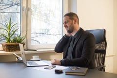 Uomo d'affari che lavora al computer portatile nella ferita del collo dell'ufficio fotografia stock