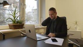 Uomo d'affari che lavora al computer portatile nella ferita del collo dell'ufficio archivi video