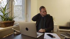Uomo d'affari che lavora al computer portatile nella ferita del collo dell'ufficio video d archivio