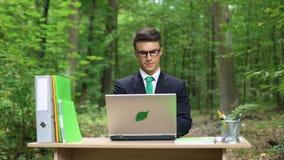 Uomo d'affari che lavora al computer portatile in parco che fa innovazione nella conservazione della natura video d archivio