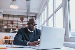 Uomo d'affari che lavora al computer portatile in ufficio Immagine Stock