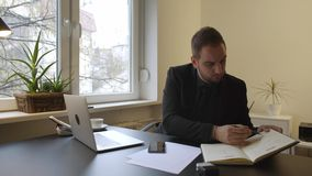 Uomo d'affari che lavora al computer portatile in ufficio che prende le note e deludente con i risultati archivi video