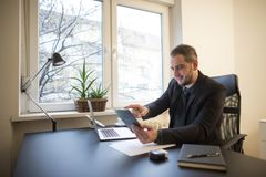 uomo d'affari che lavora al computer portatile in ufficio che prende le note sulla compressa fotografie stock