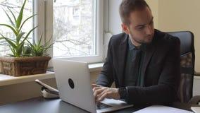 uomo d'affari che lavora al computer portatile in ufficio che prende le note sulla compressa archivi video