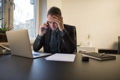 uomo d'affari che lavora al computer portatile in ufficio che rende telefonata nervosa ed arrabbiata immagini stock libere da diritti