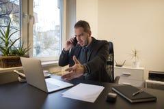 uomo d'affari che lavora al computer portatile in ufficio che rende telefonata nervosa ed arrabbiata fotografie stock