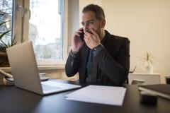 uomo d'affari che lavora al computer portatile in ufficio che rende telefonata nervosa ed arrabbiata fotografia stock