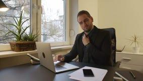 Uomo d'affari che lavora al computer portatile in ufficio che ripara un legame archivi video