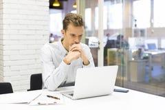 Uomo d'affari che lavora al suo computer portatile sull'ufficio nella partenza Fotografie Stock