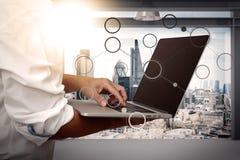 Uomo d'affari che lavora al suo computer portatile in ufficio con la città di Londra Immagine Stock