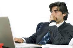 Uomo d'affari che lavora al suo scrittorio sul suo computer portatile Immagine Stock Libera da Diritti