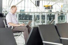 Uomo d'affari che lavora all'aeroporto durante il viaggio d'affari immagini stock libere da diritti