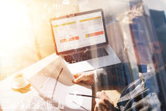 Uomo d'affari che lavora all'ufficio sul computer portatile Documenti cartacei della tenuta dell'uomo in mani Concetto dello sche fotografia stock