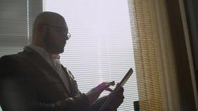 Uomo d'affari che lavora alla compressa digitale vicino alla finestra nell'ufficio Uomo che per mezzo del ridurre in pani digital archivi video