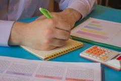 Uomo d'affari che lavora alla scrivania con il calcolatore, una penna ed il documento Contando i numeri ed effettuare i calcoli immagini stock