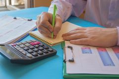 Uomo d'affari che lavora alla scrivania con il calcolatore, una penna ed il documento Contando i numeri ed effettuare i calcoli fotografie stock