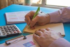 Uomo d'affari che lavora alla scrivania con il calcolatore, una penna ed il documento Contando i numeri ed effettuare i calcoli immagini stock libere da diritti