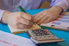 Uomo d'affari che lavora alla scrivania con il calcolatore, una penna ed il documento Contando i numeri ed effettuare i calcoli immagine stock