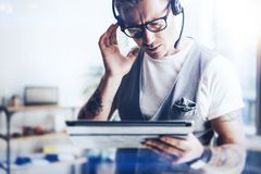 Uomo d'affari che lavora alla sua tenuta digitale della compressa in mani Uomo elegante che indossa audio cuffia avricolare e che fotografia stock