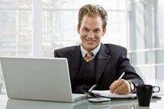 Uomo d'affari che lavora allo scrittorio Immagine Stock Libera da Diritti