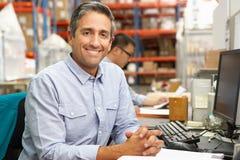 Uomo d'affari che lavora allo scrittorio in magazzino Fotografia Stock