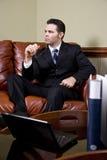 Uomo d'affari che lavora allo strato che pensa nell'ufficio Fotografie Stock
