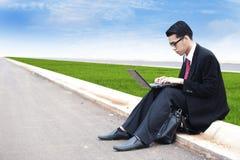 Uomo d'affari che lavora con il computer portatile esterno Immagine Stock Libera da Diritti