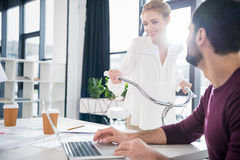 Uomo d'affari che lavora con il computer portatile sul posto di lavoro in ufficio, ciclismo della donna dietro Immagine Stock