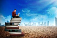 Uomo d'affari che lavora con il computer portatile sulla cima dei libri Fotografia Stock Libera da Diritti