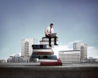 Uomo d'affari che lavora con il computer portatile sulla cima dei libri Fotografie Stock
