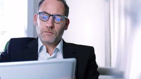 Uomo d'affari che lavora con il PC della compressa archivi video