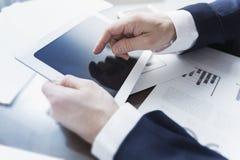 Uomo d'affari che lavora con la compressa digitale all'ufficio immagini stock