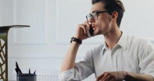Uomo d'affari che lavora con le carte e lo smartphone in ufficio ritratto bello dell'avvocato 4k di legge bello stock footage