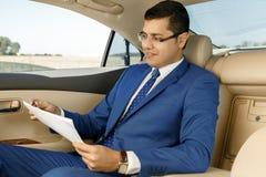 Uomo d'affari che lavora con le carte in sedile posteriore dell'automobile Fotografia Stock