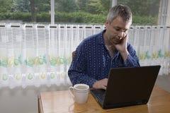 Uomo d'affari che lavora dalla casa in pigiami fotografie stock libere da diritti