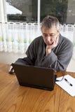 Uomo d'affari che lavora dalla casa in pigiami fotografia stock libera da diritti