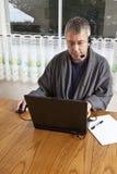 Uomo d'affari che lavora dalla casa in pigiami fotografia stock