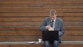Uomo d'affari che lavora mentre mangiando all'aperto stock footage