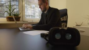 Uomo d'affari che lavora negli occhiali di protezione di realtà virtuale dell'ufficio che lo aspettano stock footage