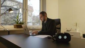 Uomo d'affari che lavora negli occhiali di protezione di realtà virtuale dell'ufficio che lo aspettano archivi video