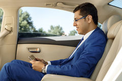 Uomo d'affari che lavora nel sedile posteriore di un'automobile Immagine Stock Libera da Diritti