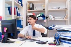 Uomo d'affari che lavora nell'ufficio con i mucchi dei libri e delle carte Immagine Stock